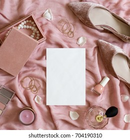 Beauty & fashion blog concept. Stylish feminine accessories flatlay on pink textile background top view. Woman makeup items, shoes, perfume, jewellery box, cosmetics, white empty paper card mockup