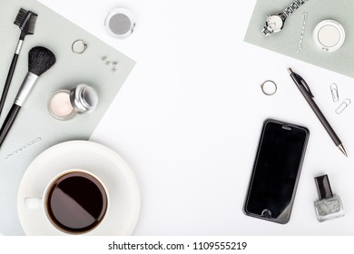 beauty and fashion blog or online shop concept. professional decorative cosmetics, makeup tools, accessory, phone and coffee mug on white background with copy space for text. flat lay frame, top view