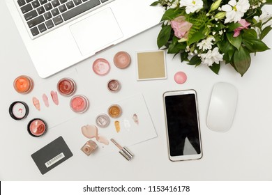 Beauty or fashion blogger workplace. Top view of feminine desk with laptop and make up samples. Blogger or freelancer home office desk. Flat lay, top view.