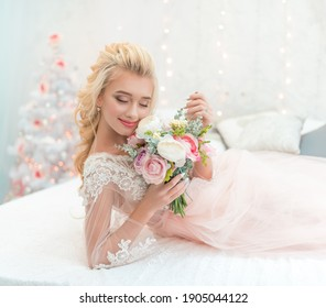 Beauty fashion bride in winter decor with bouquet of flowers in her hands. Beautiful Bride portrait wedding makeup and hairstyle. Fashion bride model in luxury wedding dress.