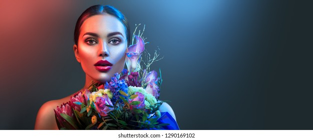 Beauty fashion brunette girl with bouquet of flowers. Glamour Sexy woman in colorful neon lights, makeup. Beautiful holiday face make-up. Trends. On dark background.