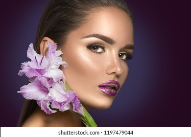 Beauty fashion brunette girl face make-up. Portrait with gladiolus flowers. Glamour Sexy woman with perfect violet trendy makeup, face contouring gradient lips. Beauty trends. On dark background.