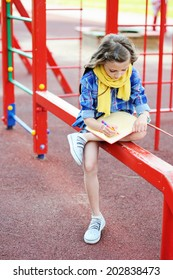 Beauty  fashion brunette school age kid girl in the blue plaid shirt, jeans skirt and yellow scarf writing in her notepad outdoor on the playground