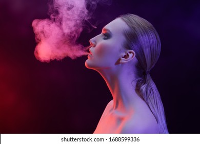 Beauty and fashion concept. Art portrait of a gorgeous woman with dark make-up smoking in red light on a black background.