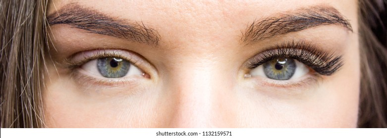 Beauty and fashion concept - Eyelash Extension Procedure. Before and after. Woman Eyes with Long false Eyelashes. Close up macro shot