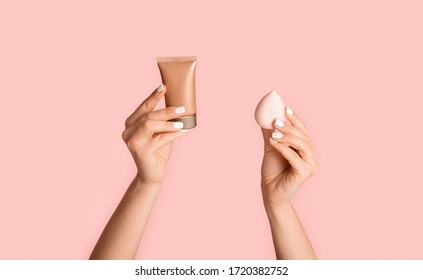 Beauty and fashion concept. Young girl holding tube with foundation and cosmetic sponge on pink background, closeup. Panorama