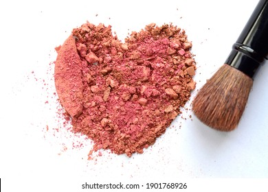 Beauty fashion creativity concept photo of heart shape of broken blush color cosmetic powder and makeup brush kit on white background.