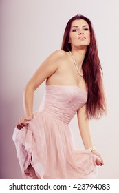 Beauty, fashion and elegant people concept - young brunette slim woman in bright dress bare shoulders