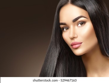 Beauty fashion girl face portrait, brunette young woman closeup. Healthy long black hair, trendy wide eyebrows, perfect makeup. Contouring make up and smooth shiny straight hair.