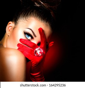 Beauty Fashion Glamorous Model Girl Portrait. Vintage Style Mysterious Woman Wearing Red Glamour Gloves. Jewellery. Jewelry. Holiday Hairstyle and Make-up. Diamond Ring. Retro Lady with Blue Eyes