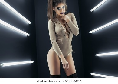 Beauty fashion glamour model girl in a bathing suit body posing and having fun over black background,sexy woman with curly hairstyle,makeup,skin care body cream, long legs,girl with a beautiful tan