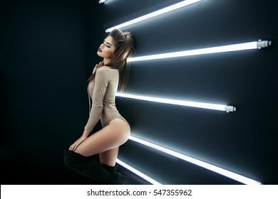 Beleza moda glamour modelo menina em um corpo de maiô posando e se divertindo sobre o fundo preto, mulher sexy com penteado encaracolado, maquiagem, creme de corpo cuidado da pele, pernas longas, menina com um belo bronzeado