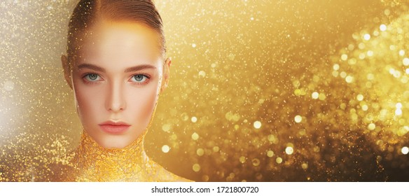 Beauty, fashion gold concept. Portrait of a beautiful girl model with golden skin and golden make-up on a sparkling background with golden lights. Jewelry. Cosmetics and beauty care. Copy space.