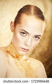 Beauty, fashion gold concept. Portrait of a beautiful girl model with golden skin and golden make-up on a glowing gold background. Jewelry. Cosmetics and beauty care.