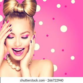 Beauty fashion happy model girl with funny bow hairstyle, pink nail art and makeup over polka dots background. Laughing retro styled young woman