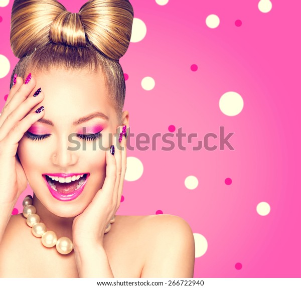 Beauty Mode Happy Model Girl mit lustiger Bogen-Frisur, rosafarbene Nagelkunst und Make-up auf Polka-Punkte-Hintergrund. Laughing retro stilisierte junge Frau