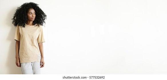 Beauty and fashion. Indoor isolated shot of beautiful stylish woman with Afro haircut wearing oversize t-shirt and cotton pants posing at white studio wall with copy space for your advertising concept