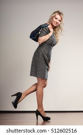 Beauty and fashion. Middle aged blonde business woman in full length wearing gray dress high heels shoes holds handbag, studio shot on gray