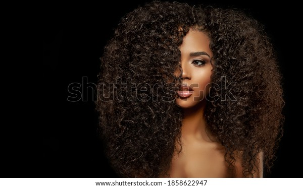 Beauty Fashion model. Black woman face & beautiful voluminous hair. Afro american girl. Beauty skin female face.  Healthy hair with luxurious Updo haircut. Waves, Curls volume Hairstyle. Hair Salon.