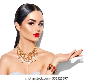 Beauty fashion model brunette girl portrait. Sexy young woman with perfect makeup and trendy golden accessories showing empty copy space on the open hand palm for text, fashion glamour female