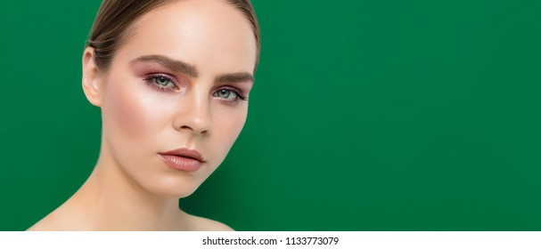 Beauty Fashion Model Face portrait with Perfect Professional Make Up  against Green Background. Web Site Template Banner. Cosmetology and Cosmetics advertising.