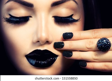 Beauty Fashion Model Girl with Black Make up, Long Lushes. Fashion Trendy Caviar Black Manicure. Nail Art. Dark Lipstick and Nail Polish. Isolated over black background