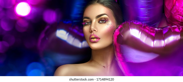 Beauty fashion model girl creative art makeup, over purple, pink and violet air balloons background. Woman face Make-up with gems, pink with gold lips, purple eyeshadows. Widescreen.