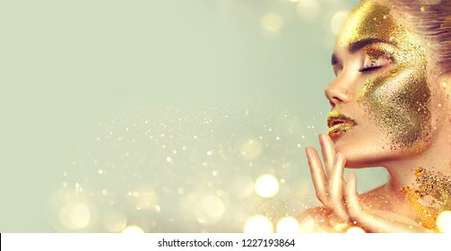 Beauty fashion model girl with Golden skin make up and body, golden jewellery background. Gold body art. Metallic, glance beautiful lady touching face. Border Fashion art portrait, make up, gift