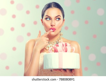Beauty fashion model girl holding Beautiful Big Cake and tasting sweet cream on it. Funny joyful styled woman with wedding, party or birthday cake. Diet, dieting concept. Slimming, weight loss