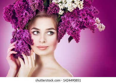 Beauty fashion model Girl with Lilac Flowers Hairstyle. Nature. Hairstyle. Portrait of a young woman on a white background