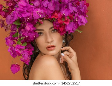 Beauty fashion model girl with pink flower on her head. Portrait on red orange background. Spa and beauty salon concept. Summer perfect shiny skin.