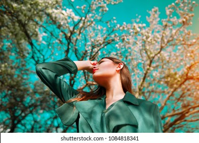 Beauty fashion model girl posing over blooming trees, enjoying nature in spring apple orchard. Beautiful brunette young woman over sky in Garden with blooming apple trees. blossom flowers outdoors