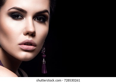 Beauty Fashion Model Girl with short hair. Brunette Model Portrait. Short haircut. Sexy Woman Makeup and Accessories. Isolated on black. Hair cut. Purple Earrings