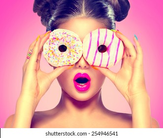 Beauty fashion model girl taking sweets and colorful donuts. Funny joyful Vogue styled woman with sweets on pink background. Diet, dieting concept. Junk food, Slimming, weight loss