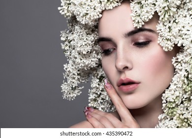 Beauty fashion model Girl with white Lilac Flowers Hair Style. Beautiful Model woman with Blooming flowers on her head. Nature Hairstyle. Summer. Creative Makeup and manicure. Make up. Vogue Style