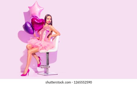 Beauty fashion model party girl with heart shaped air balloons posing, sitting on chair, Birthday party, Valentine. Holiday celebration. Beautiful young pin up brunette woman full length portrait
