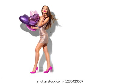 Beauty fashion model party girl with heart shaped air balloons having fun. Isolated on white posing. Valentine's Day. Air kiss. Holiday celebration. Beautiful young brunette woman full length portrait