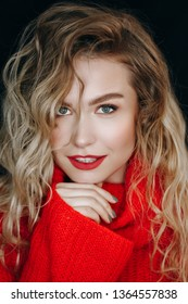 Beauty Fashion Model Portrait Backstage Make-up. Young Woman in Red Sweater Posing in Studio. Girl with Perfect Skin, Wavy Hair and Beautiful Makeup. pretty Blond Vertical Head and Shoulders Shoot