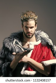 Beauty fashion model portrait. Christmas guy in santa fur coat in crown. Drag queen, homosexual and trans. Cinderella prince with shoe on grey background. Freak, gay and transvestite. Freedom and lgbt
