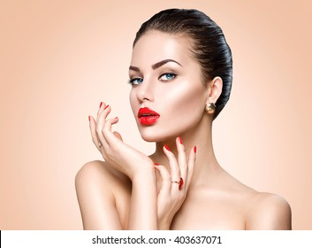 Beauty Fashion Model Woman face. Portrait with perfect skin. Red Lips and Nails. Beautiful Sexy Brunette Woman with Luxury Makeup and Manicure over beige background