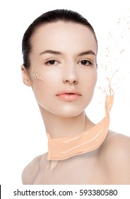 Beauty fashion model woman with liquid foundationon her cheek and foundation splash on white background