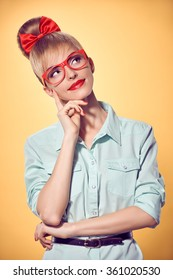 Beauty fashion nerd woman in stylish glasses thinking, idea. Attractive pretty funny blonde girl smiling.Confidence, success, Pinup hairstyle bow makeup.Unusual playful, expression.Vintage, on yellow