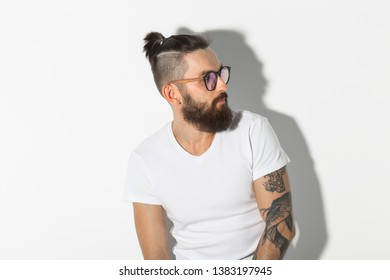 Beauty, fashion and people concept - Hipster man with beard posing over white background