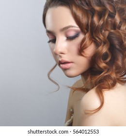 Beauty fashion portrait of a beautiful girl with a natural make-up and hairstyle curls isolated on a gray background.