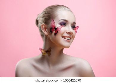Beauty fashion portrait of a beautiful smiling girl with a gentle make-up and butterflies on her face isolated on a pink background.