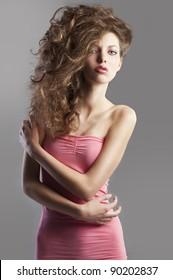 beauty fashion portrait of beautiful young brunette with curly hair flying and creative hairstyle. she looks in to the lens with face slightly raised, she touches the right arm with left hand.