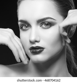 Beauty fashion portrait of caucasian brunette woman wet red lipstick and arms touching face. Isolated on black background. Black and white