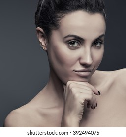Beauty Fashion Portrait of Caucasian Young Girl with Natural Nude Make Up with a hand on chin waiting for an answer and looking front on camera isolated on grey gradient background. Toned