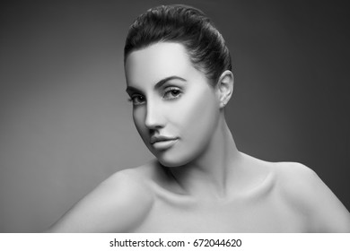 Beauty Fashion Portrait of Caucasian Young Girl with Natural Nude Make Up with brown eyes and nude shoulders on grey gradient background. Black and white
