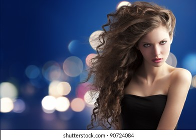 beauty fashion portrait of a very young cute brunette with long curly hair with hairstyle flying in the wind on bokeh background